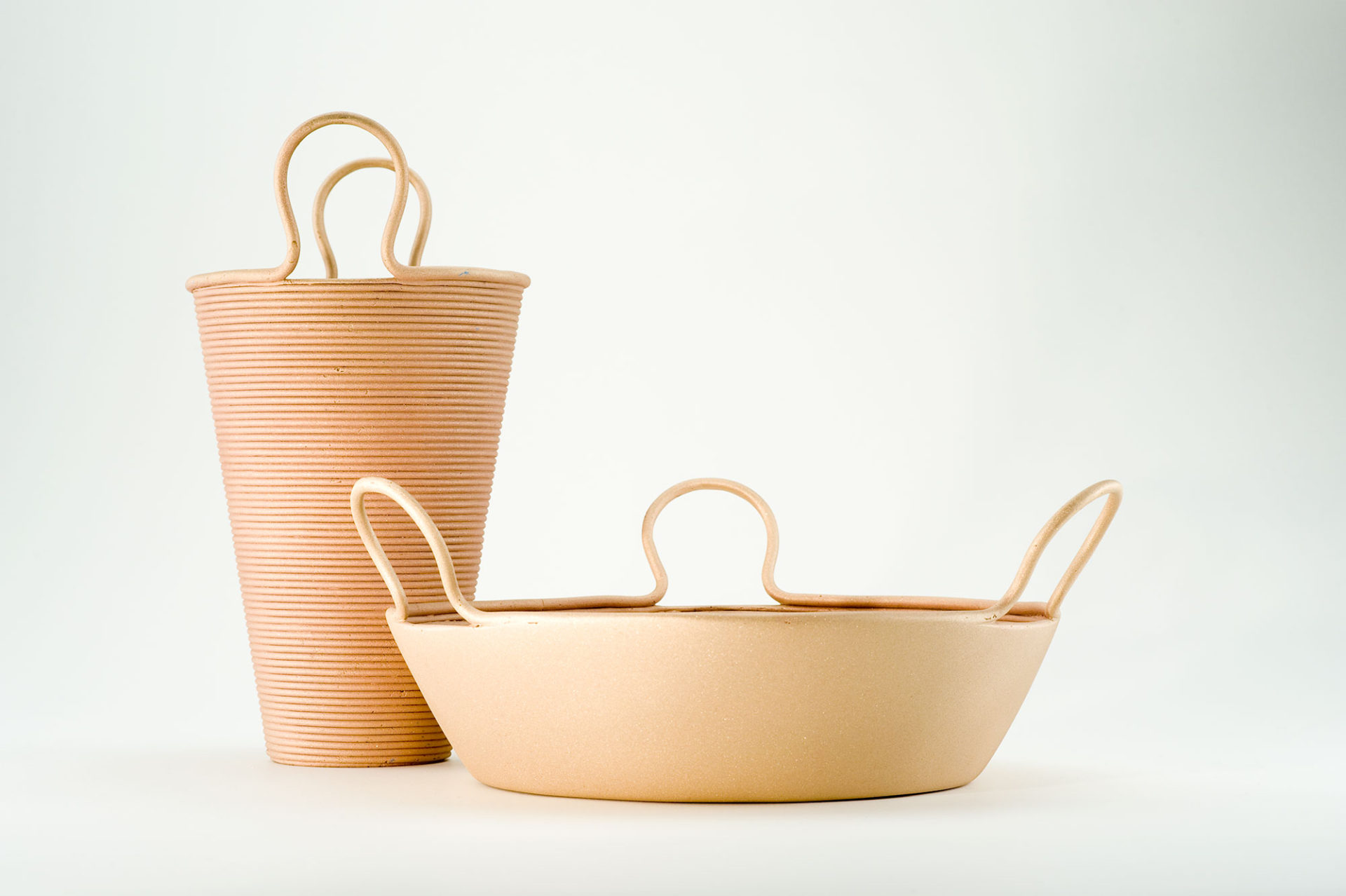 Tall straw-colored conical vase and wide conical basket, both straw-colored with handles.