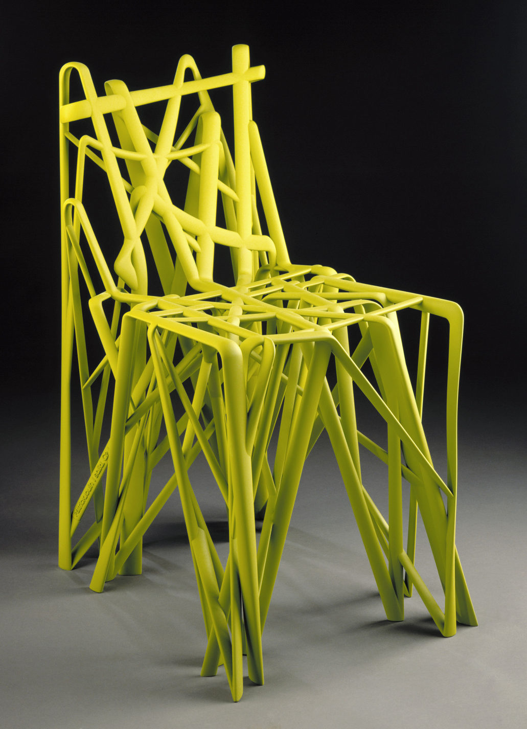 Bright yellow 3D-printed chair that appears to be made from a scribbled drawing.