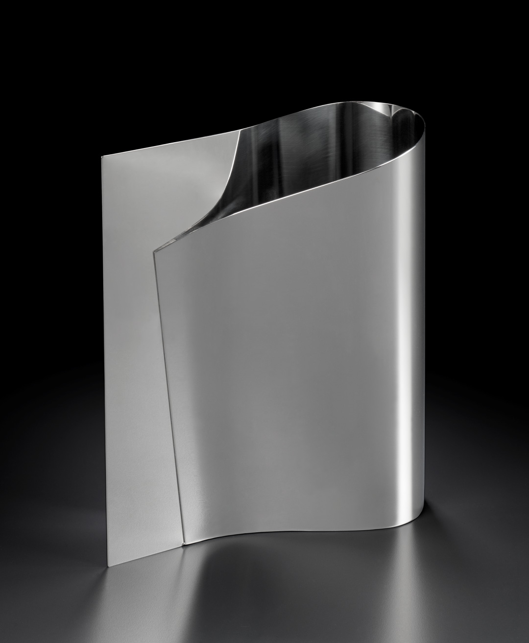 Vase. The two ends of a sheet of steel have been brought together on one side, leaving a rounded opening on the other.