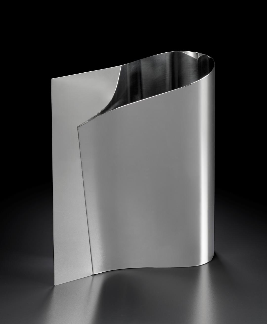 Vase. Les deux extrémités d'une feuille d'acier se rejoignent d'un côté pour former une ouverture arrondie de l'autre.