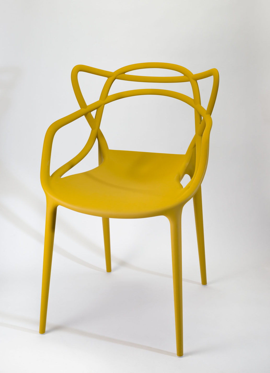 Plastic armchair in mustard yellow, with slender legs, solid seat, and open-frame back and arms.