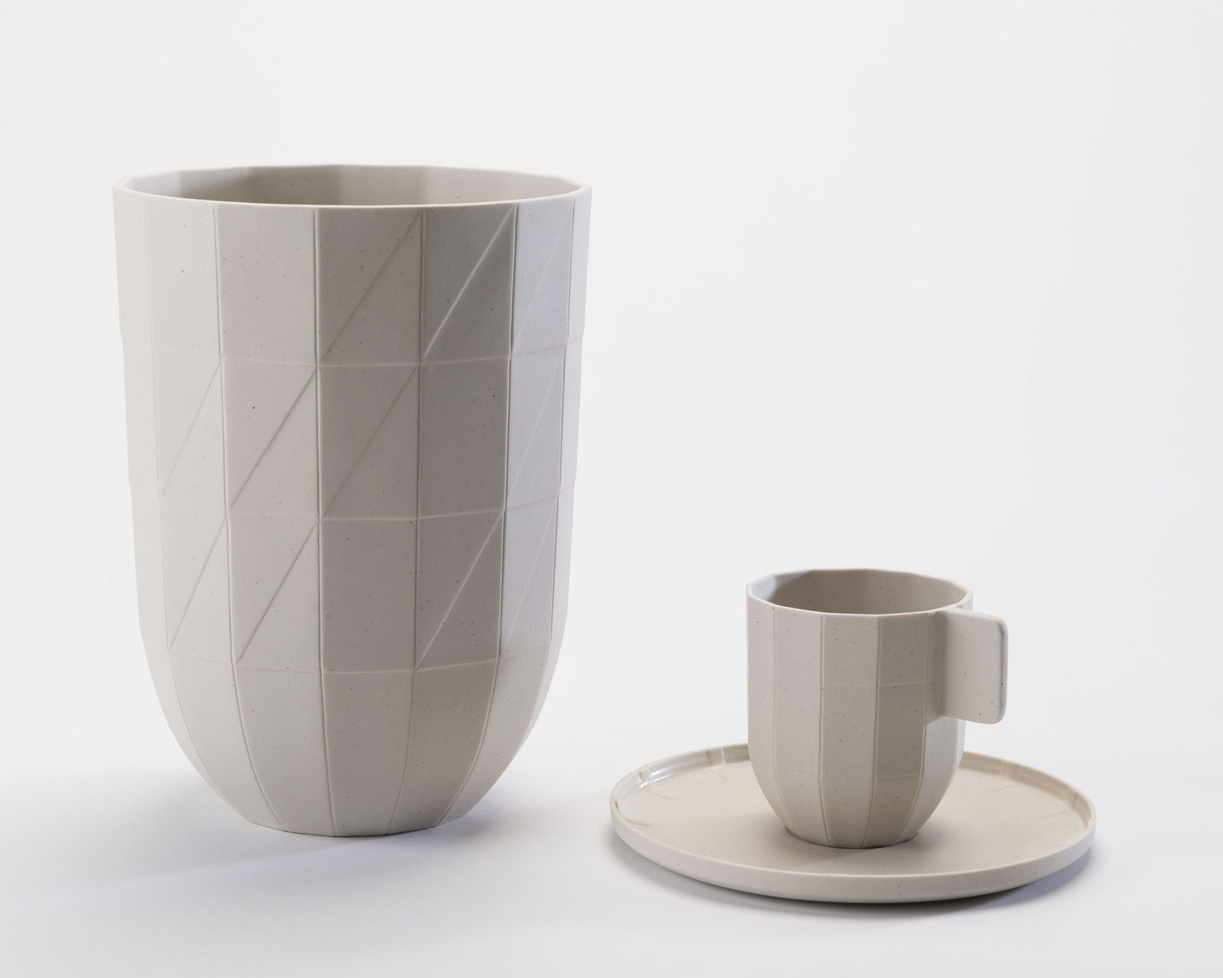 Large mug, small coffee cup and saucer. Each piece is beige porcelain and made to look like it is made of folded paper.