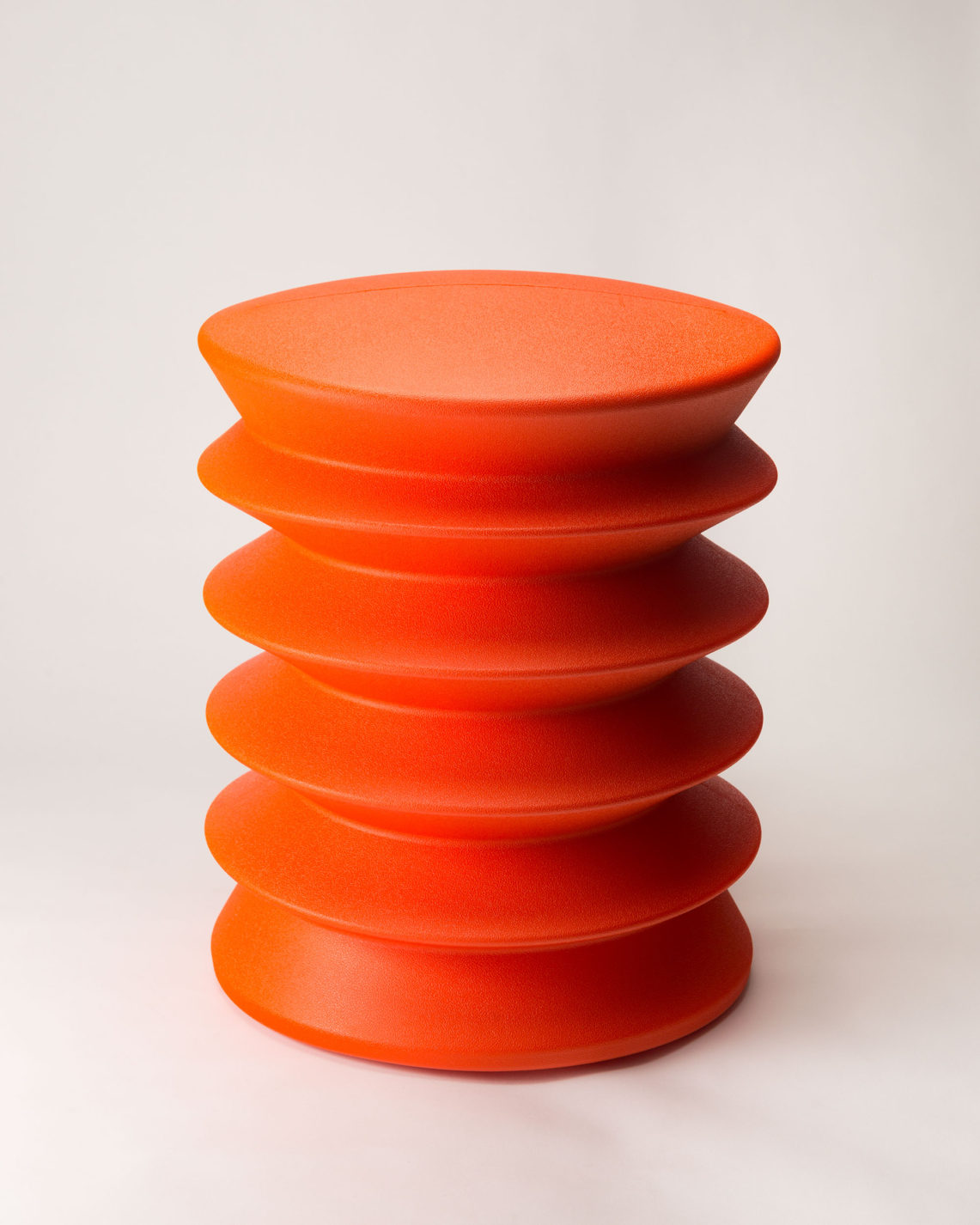 Cylindrical stool formed of a single piece of red plastic with accordion folds and a slightly rounded top.