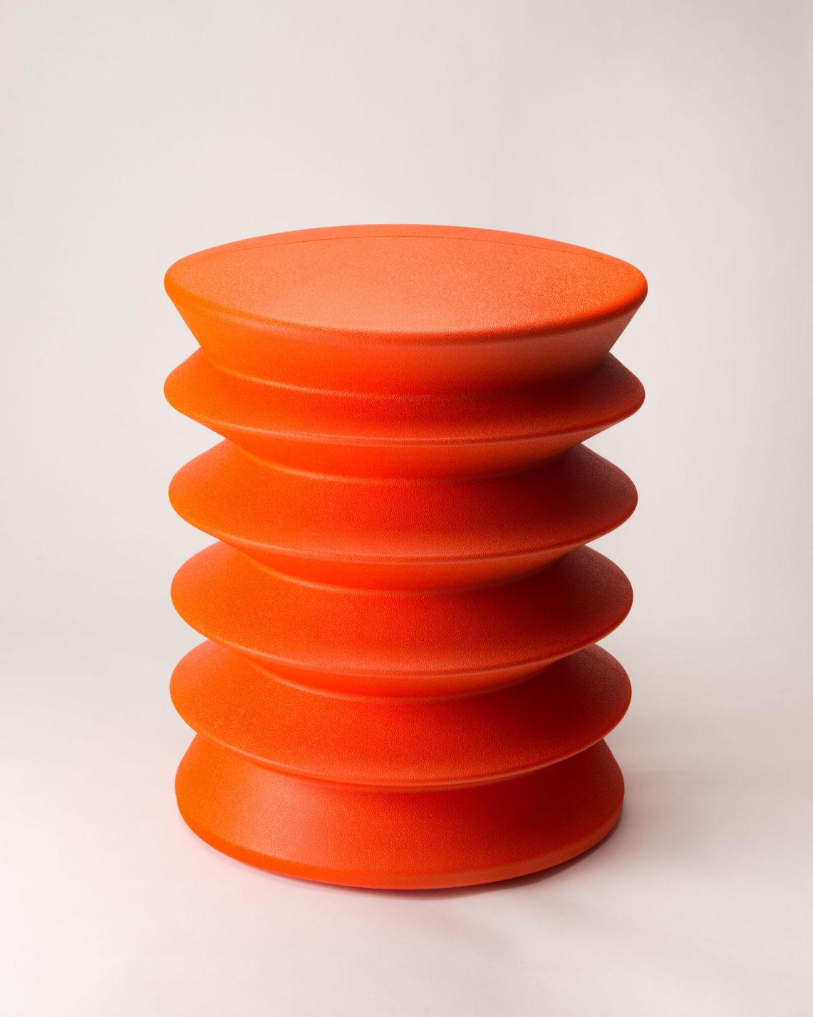 Tabouret cylindrique formé d'une seule pièce de plastique rouge pliée en accordéon au dessus légèrement bombé.