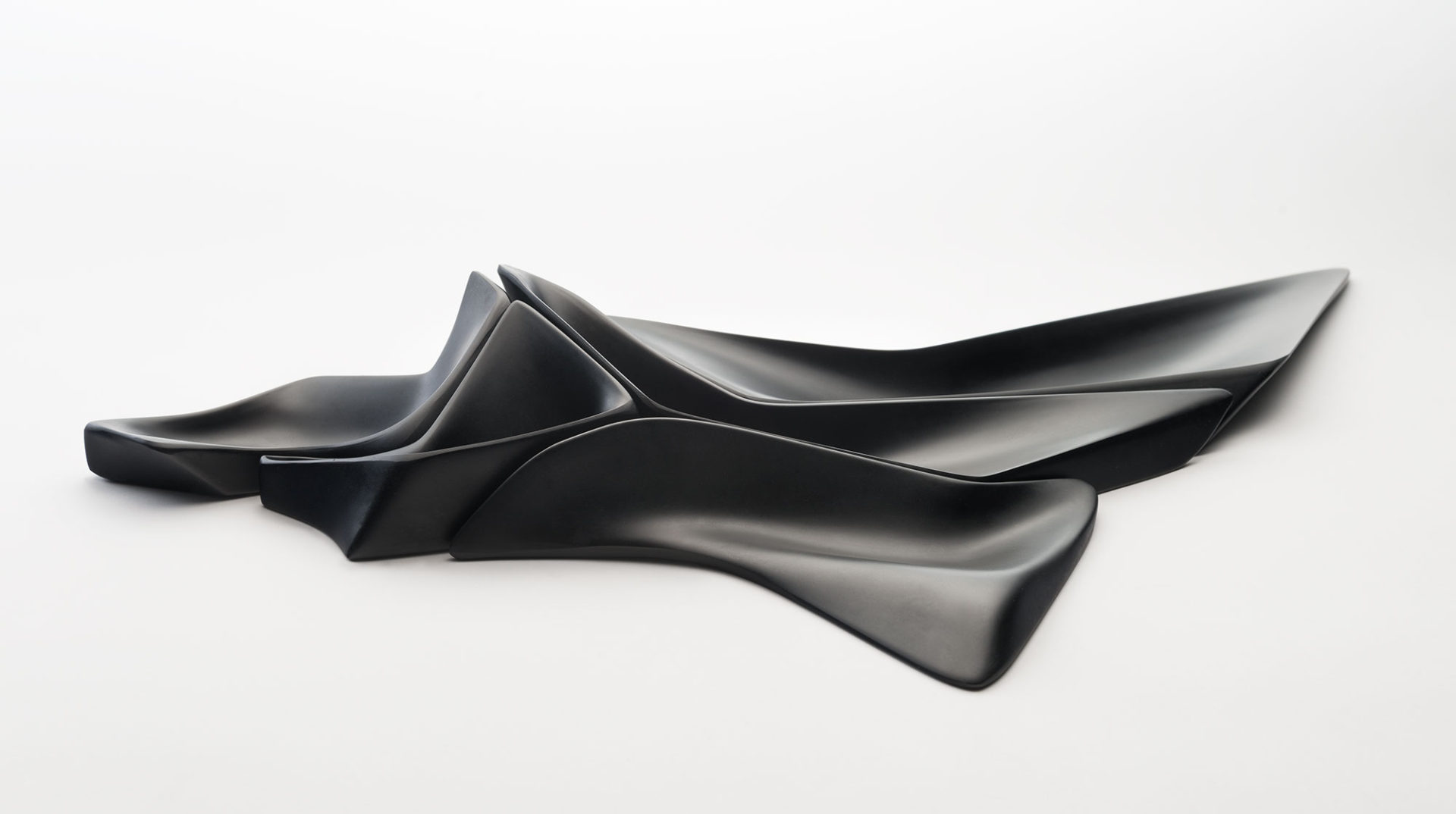 Centerpiece of five assembled elements of sculptural black plastic in various sizes and shapes that fit together like a puzzle.