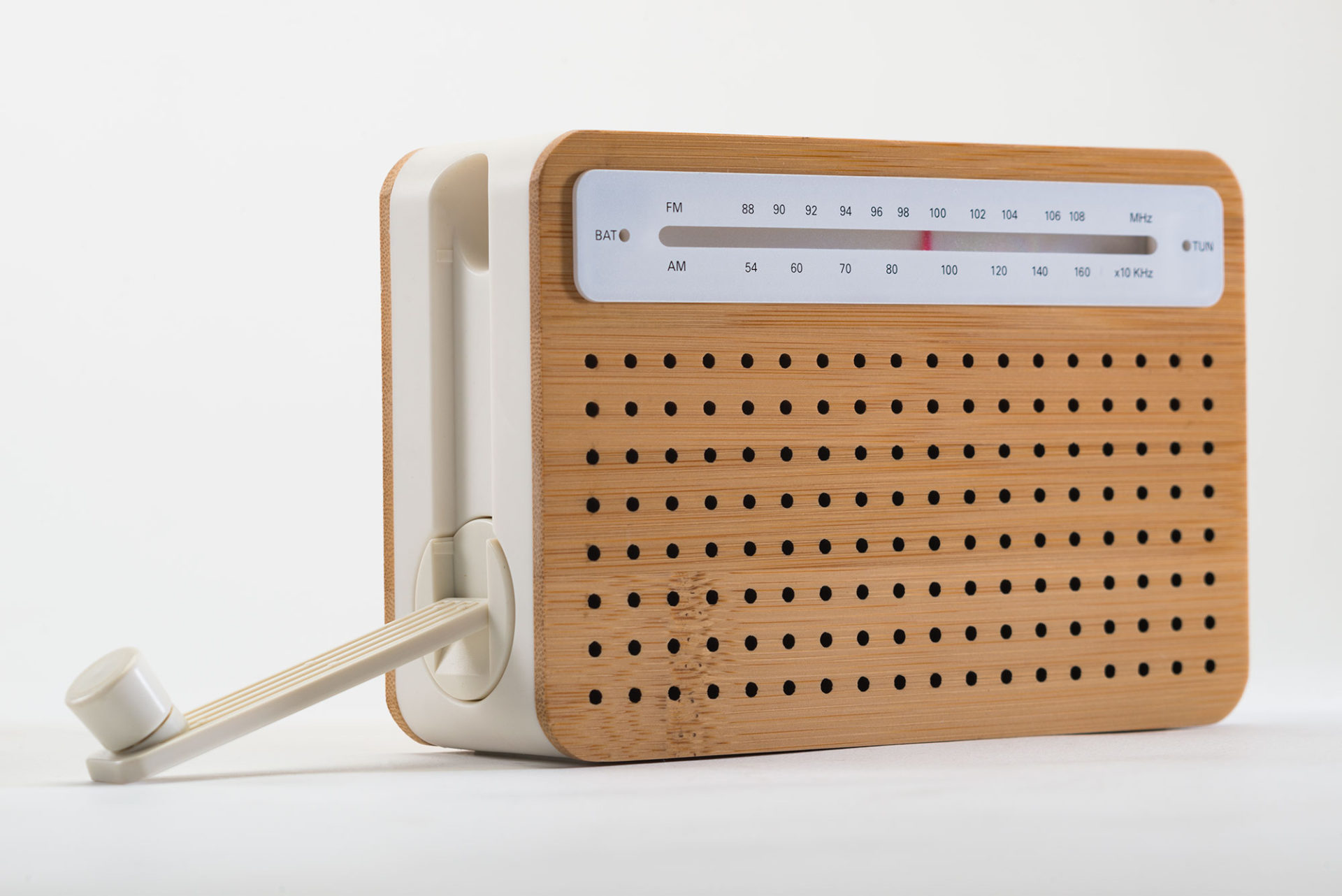 Rectangular portable radio with a perforated bamboo face, and white plastic body.