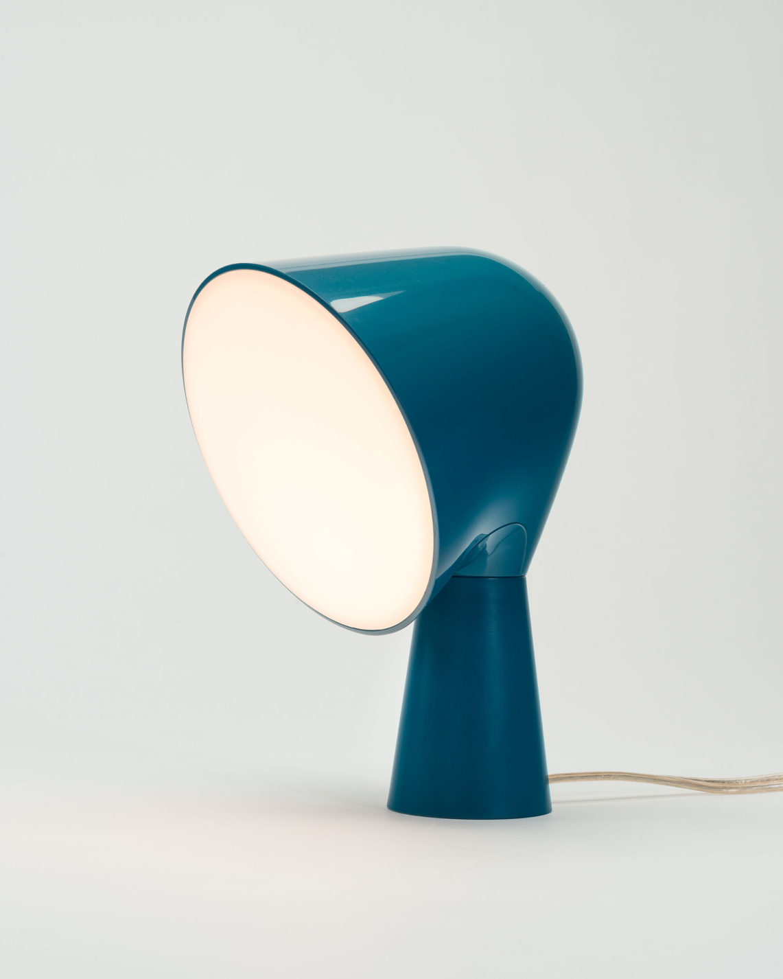 Table lamp in blue plastic with a slender conical base, wider conical top, and a translucent white disc covering the light source.