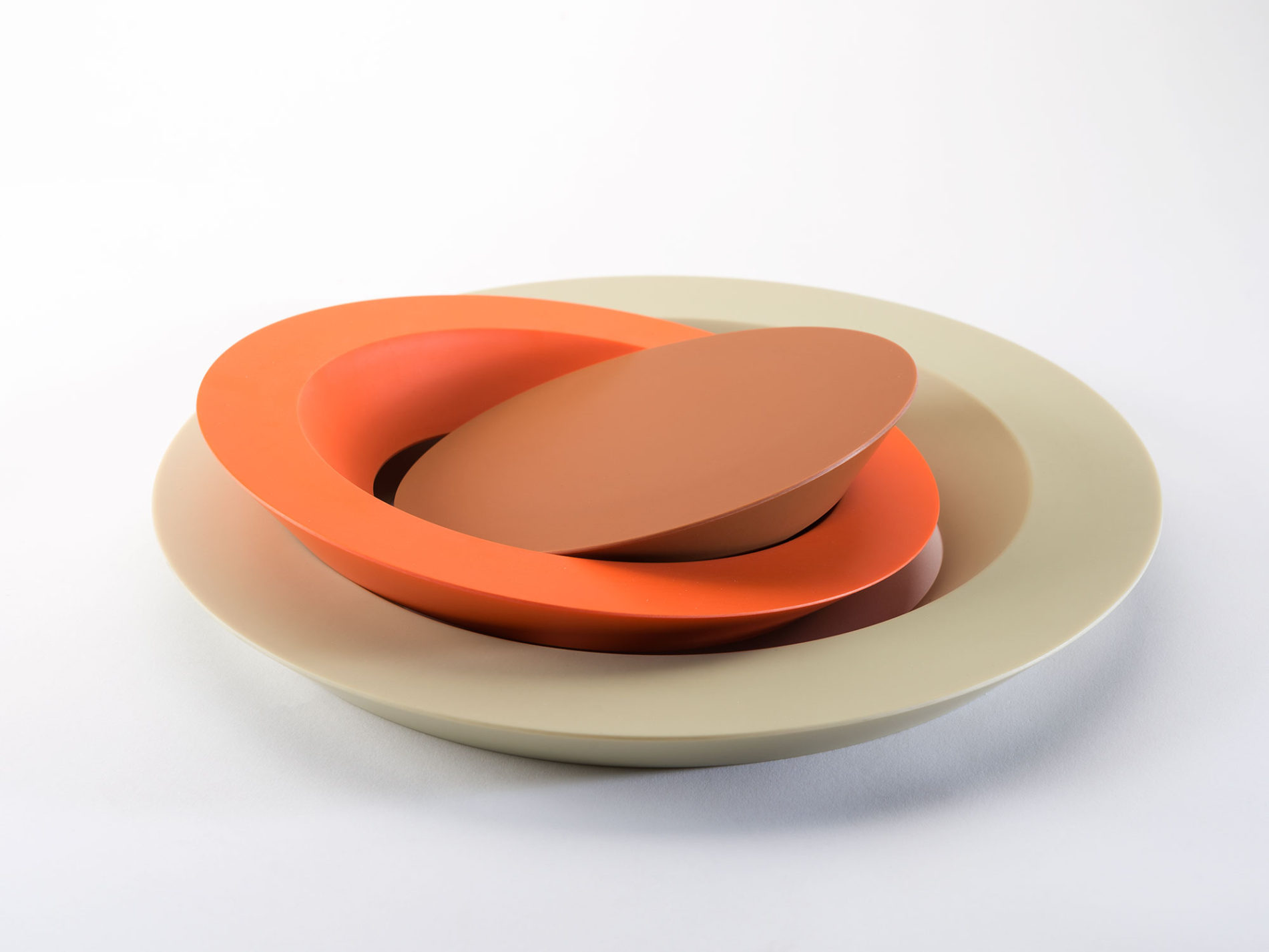Disassembled cake plate made of three concentric circles: outer ring in off-white, second ring in orange, and center circle in brown.
