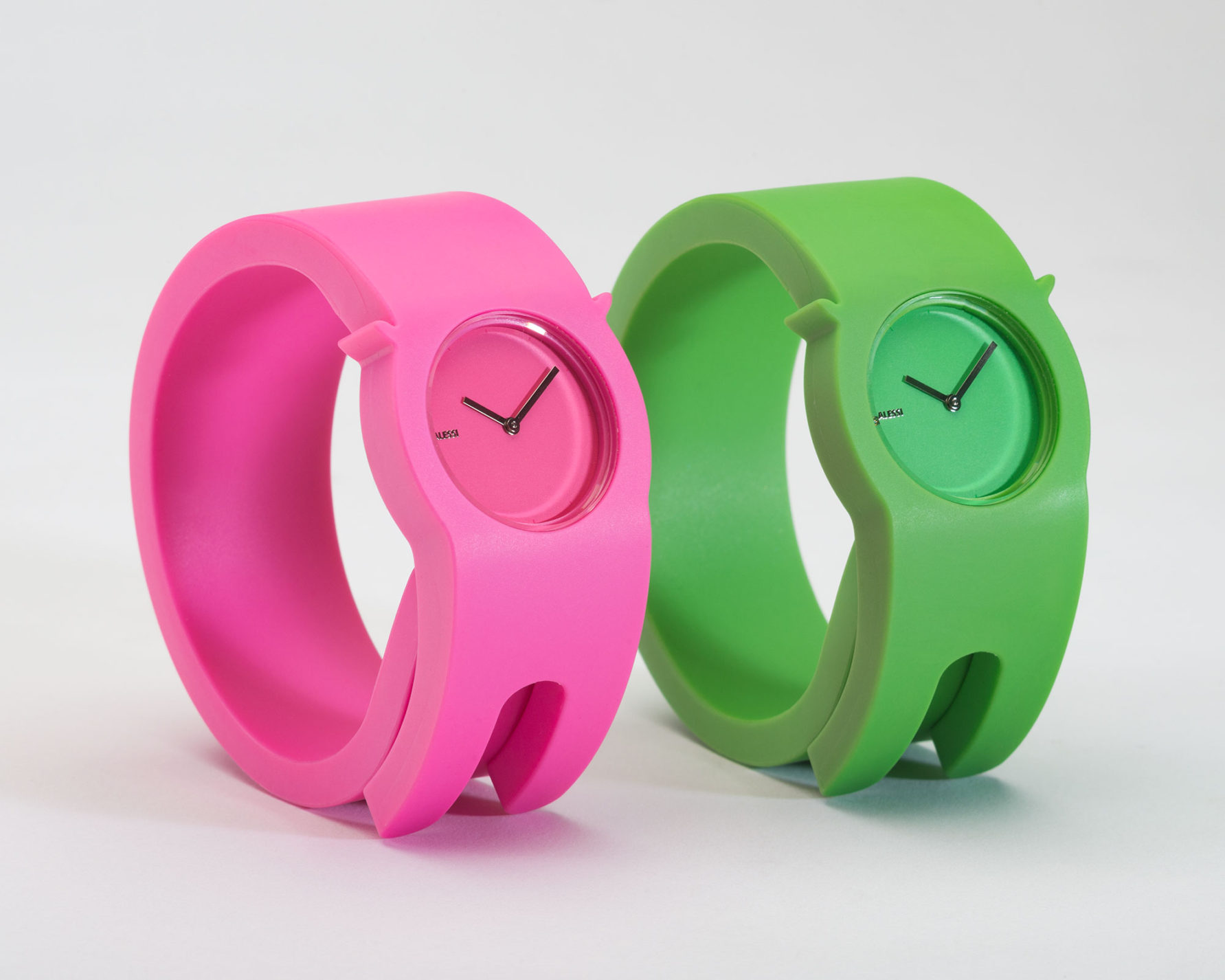 Two plastic wraparound wristwatches, one in pink, one in green, with matching-colored faces and metal hands.