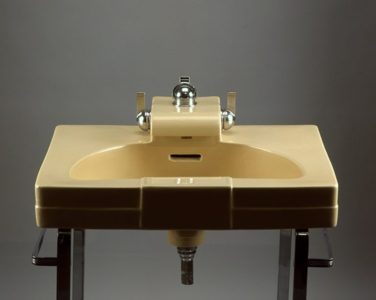 Rectangular bathroom sink with semicircular basin and dome-shaped shiny metal fixtures set on a stand of strap steel.