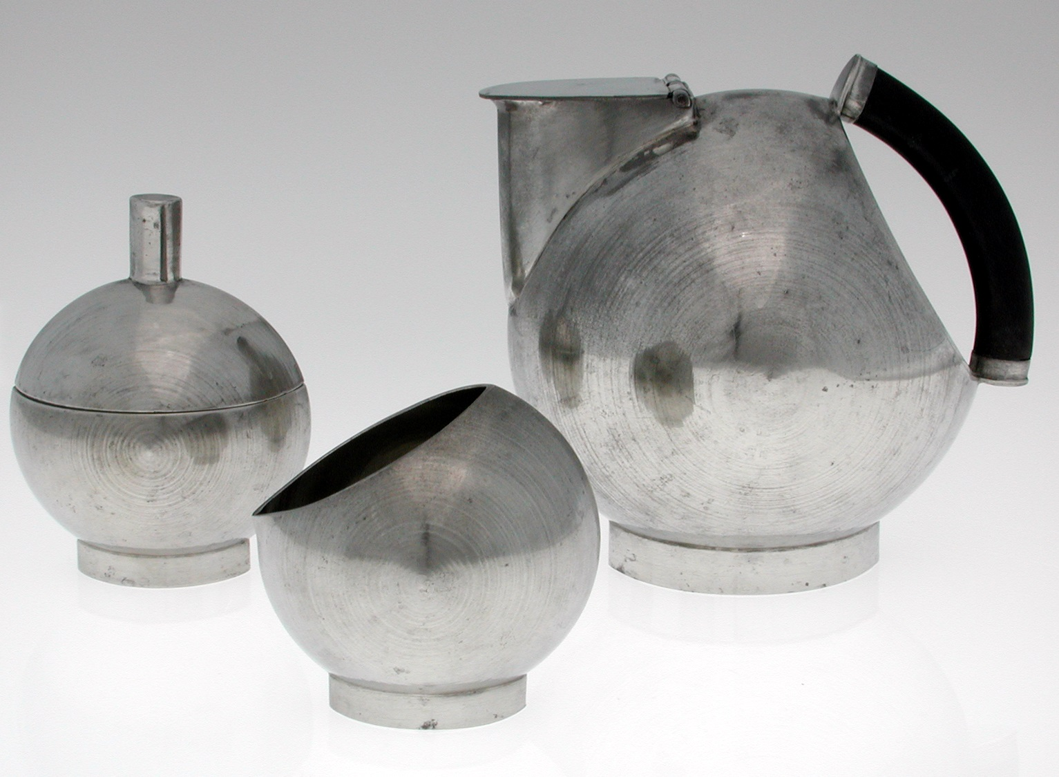 Brushed-metal coffee service. Spherical coffeepot has an arc-shaped handle