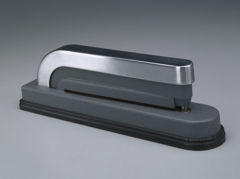 Hole punch in grey and polished metal that resembles a stapler with rounded corners.