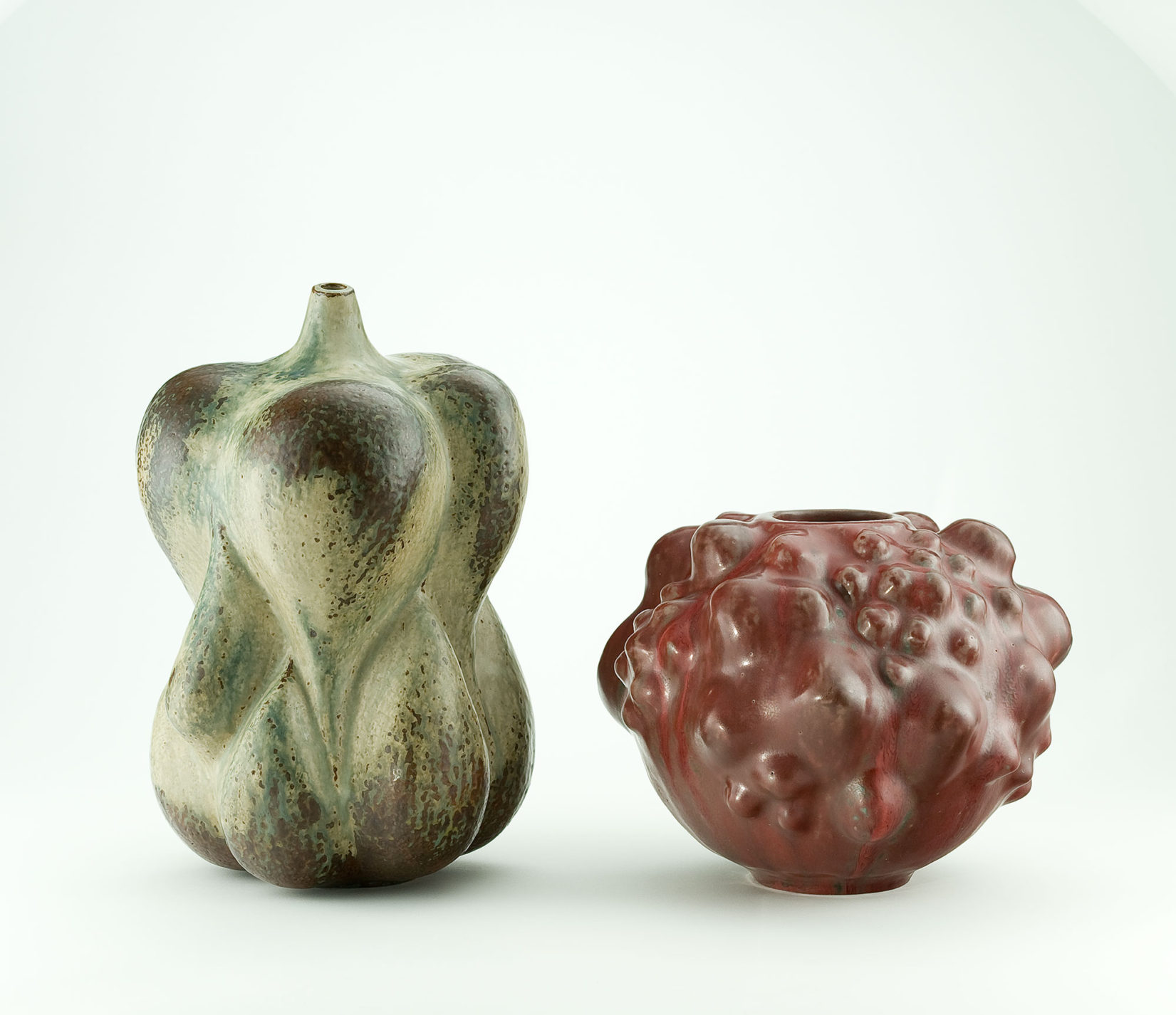 Two earthenware vases in organic forms. One in green resembles an assemblage of flower bulbs. The other in dark red has a bumpy surface like a gourd.