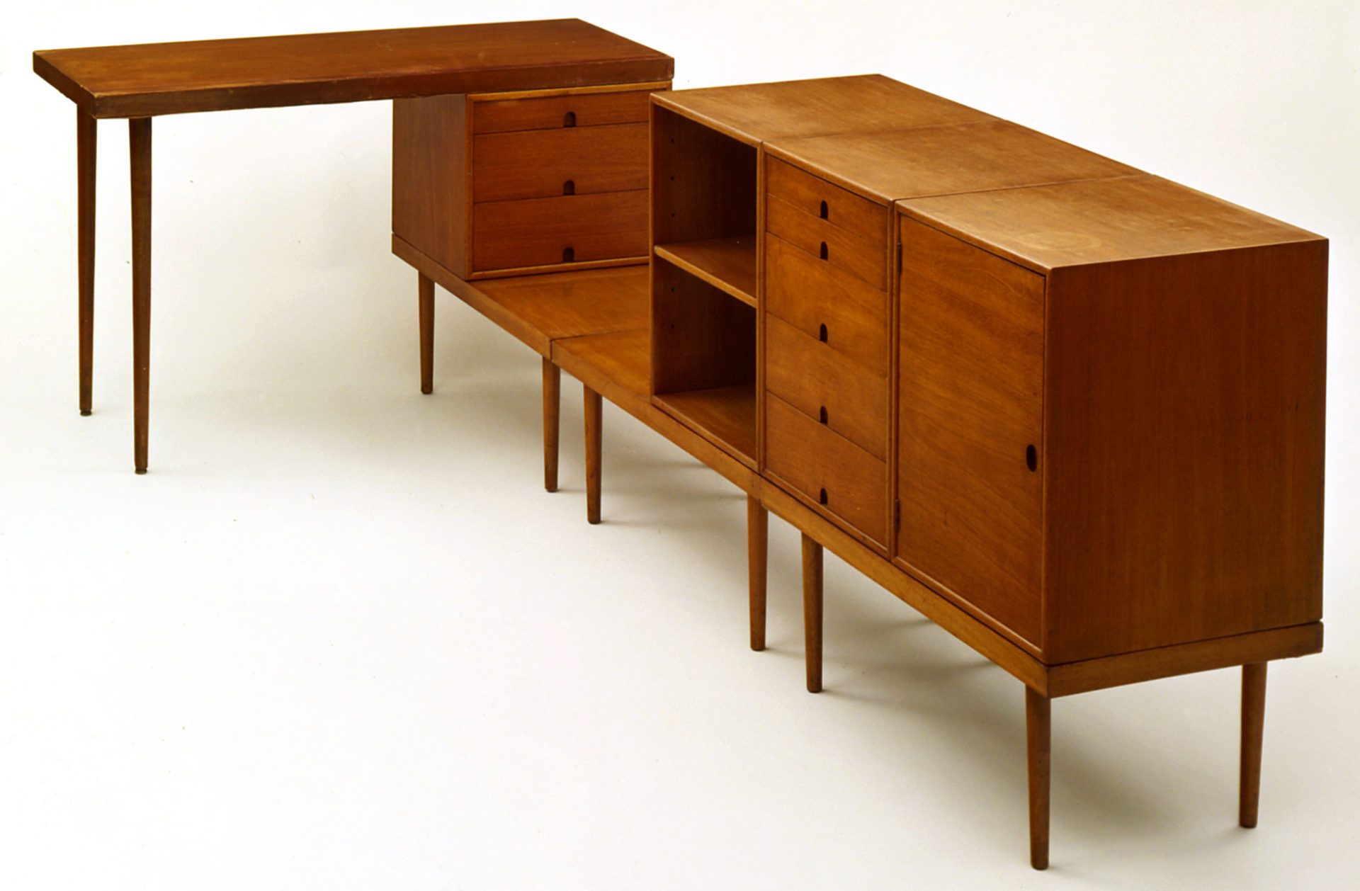 Set of modular shelves, drawers, cabinets and table surfaces in wood.