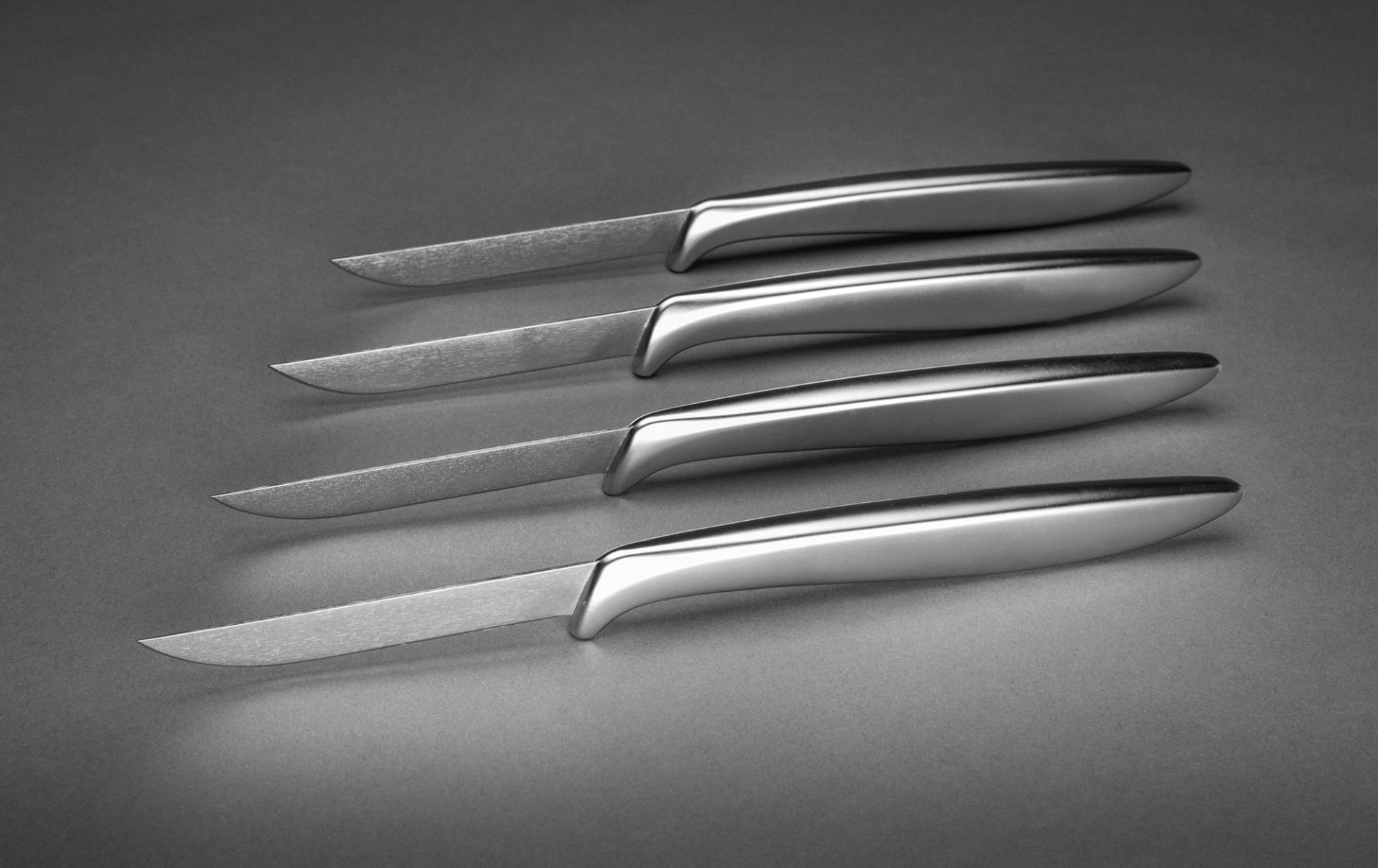 Set of four identical knives with sleek brushed-metal handles and slender steel blades.