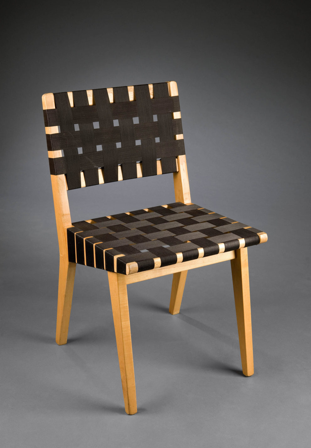 Chair with a simple wooden frame with seat and back formed by woven strips of plastic webbing.