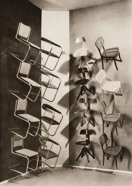 Black-and-white exhibition installation view showing a series of different side chairs, including Breuer's B32 chair, mounted up the walls in a corner of the gallery.