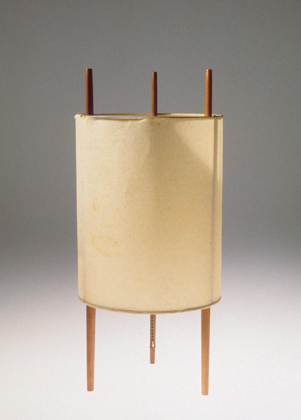 Lamp made with three vertical wooden sticks surrounded by a cylindrical lamp shade.