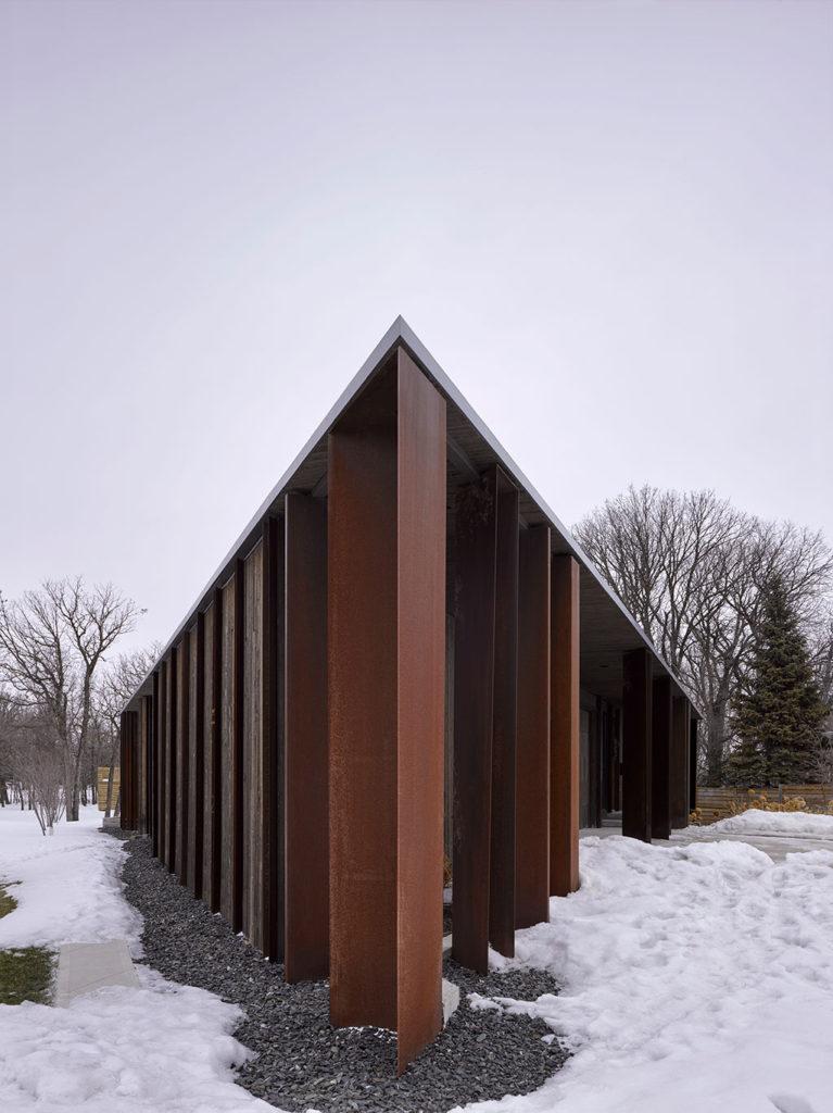 Bâtiment trapu sur piliers en métal et en bois, vu d'un des coins à angle aigu.