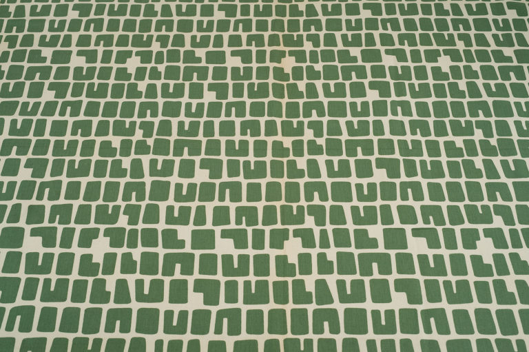 White textile with horizontal rows of blocky letter-like shapes in green.