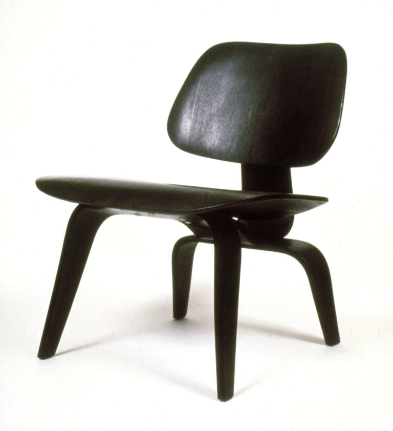 A squat black wooden chair with a shaped seat and base connected by a piece of bent wood. The back legs are shorter than the front legs.
