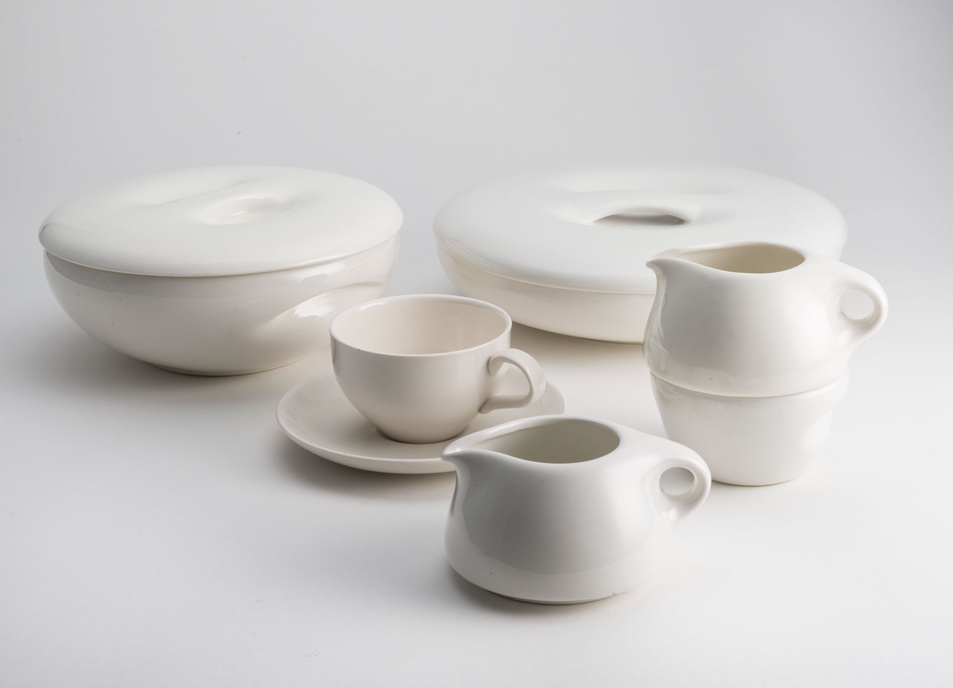 Set of white ceramic dishes. Two bowls, one shallower than the other, each have lids with indentations for handles. One stacking sugar bowl and creamer; one creamer, and one teacup and saucer.