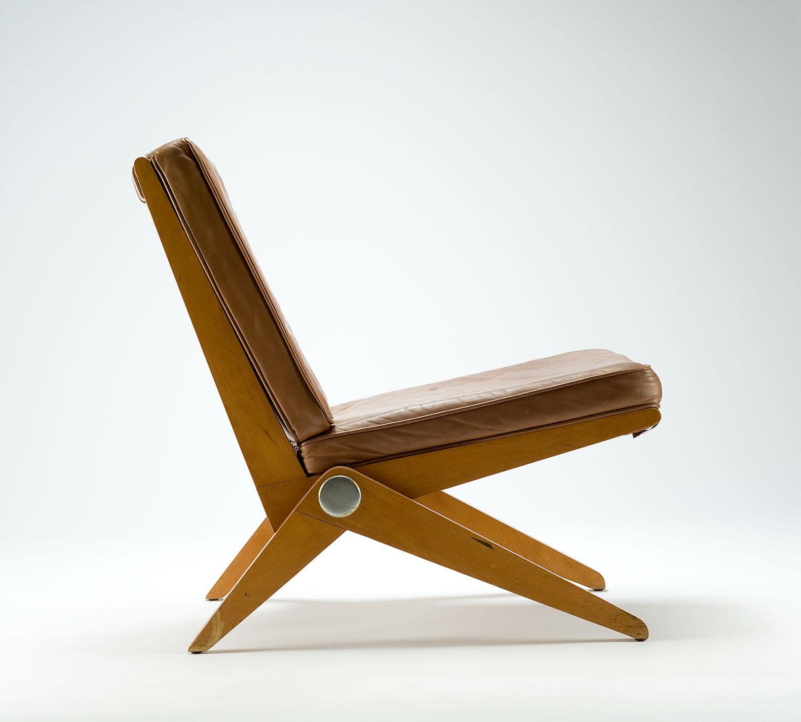 Chaise de profil. Chaise à structure de bois simple à l'assise et au dossier rembourrés avec revêtement de cuir brun. Les pattes inclinées sont raccordées à la base en un seul point, comme si la chaise reposait sur deux boomerangs.
