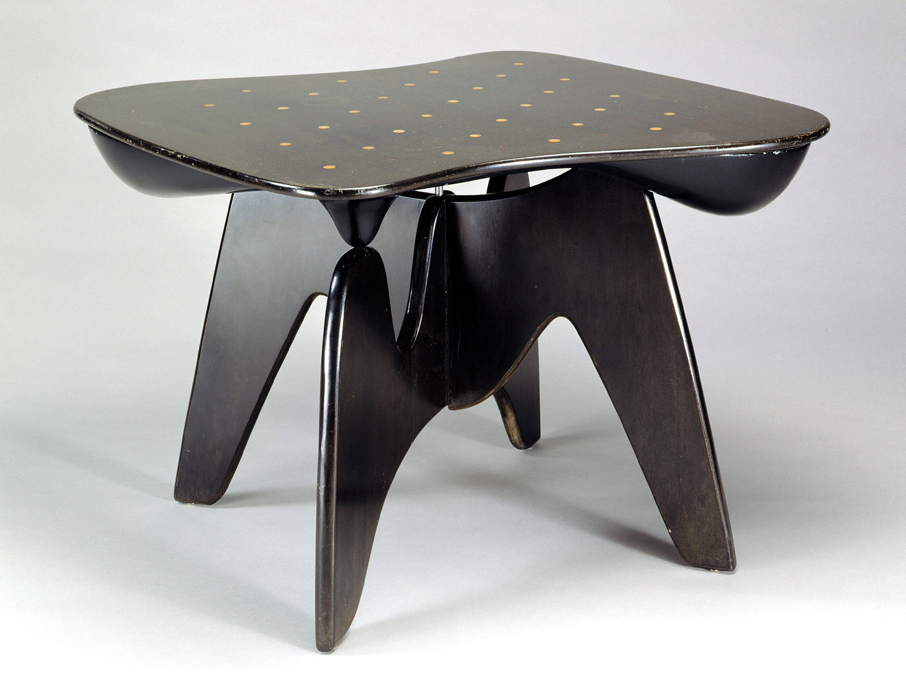 Low black table in wood with peg holes in the surface and curving sides and legs.