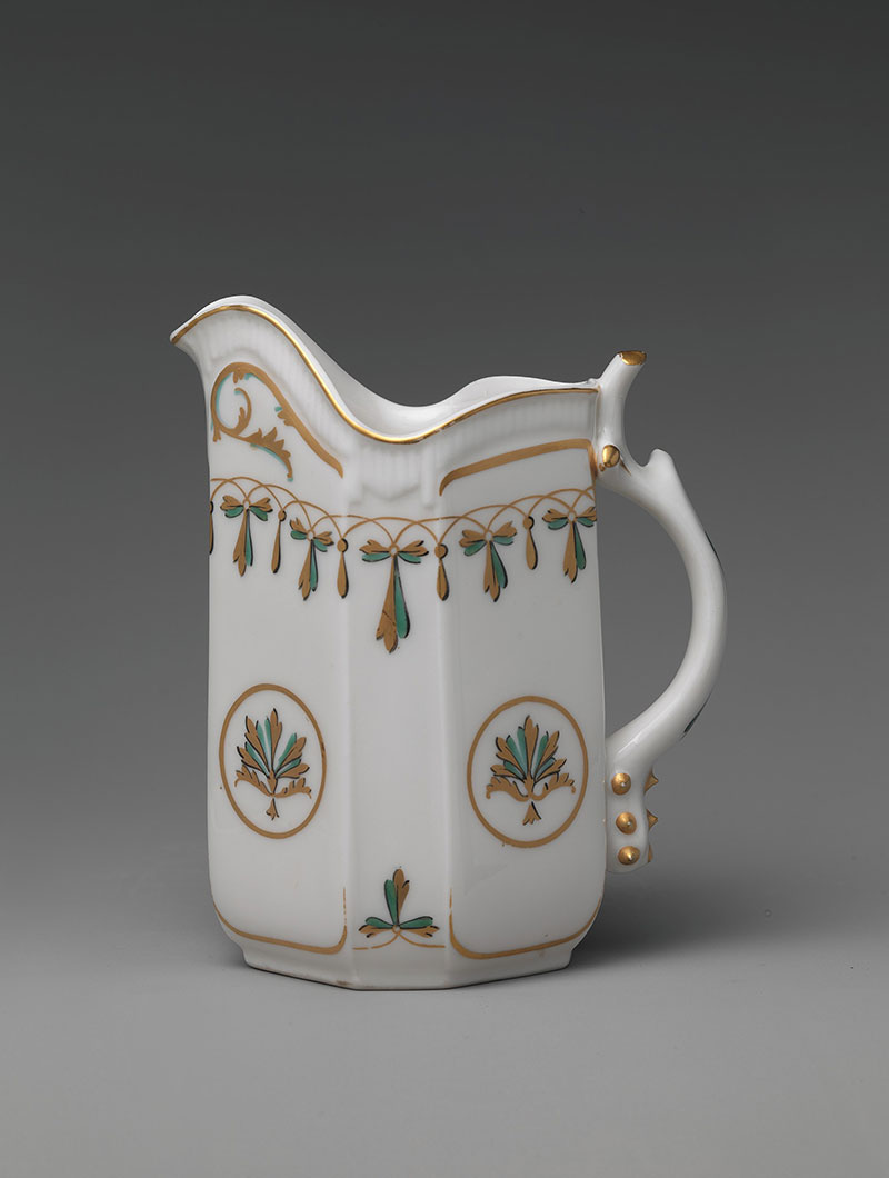 White ceramic cream pitcher with smooth sides and simple handle.