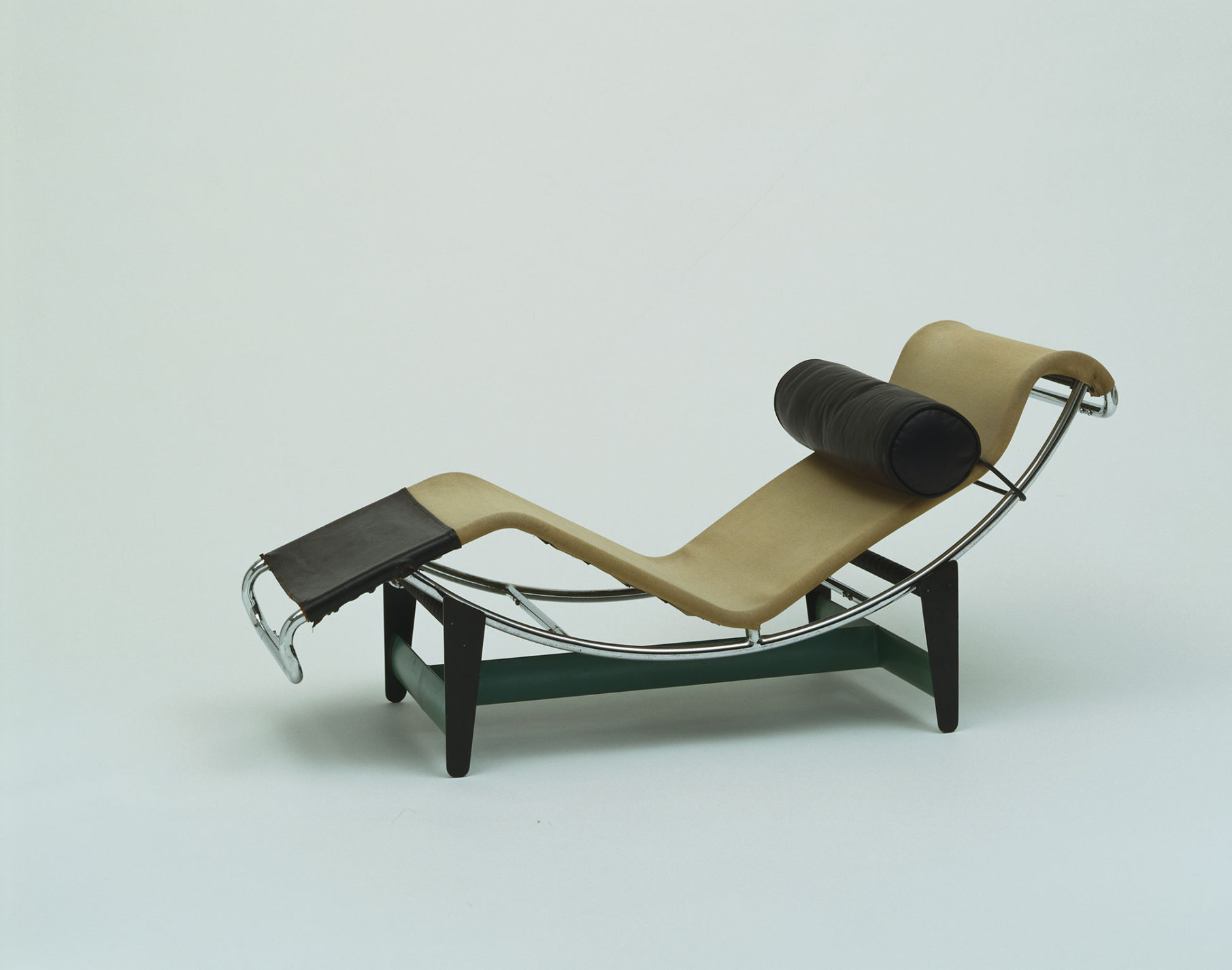 Tubular-steel framed chaise longue set on a painted metal frame with tan and black upholstery and a cylindrical black pillow.