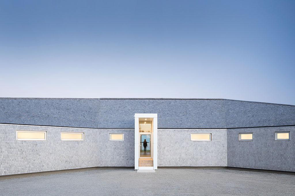 Construction trapue en bardeaux percée de petites fenêtres horizontales près du toit et d'une entrée verticale étroite.