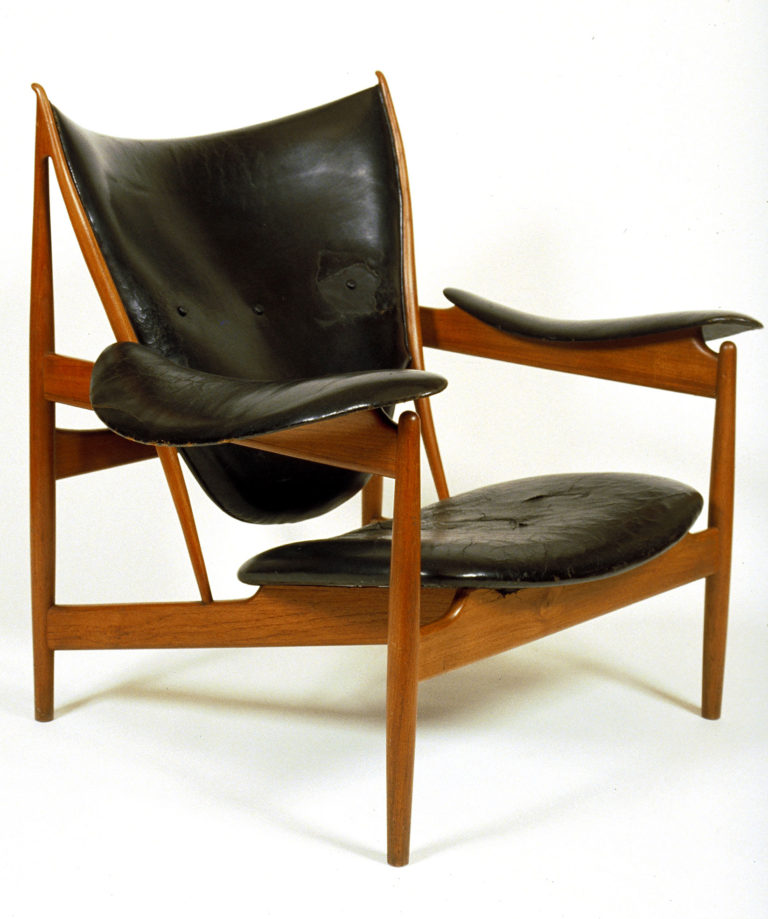 Armchair with an angular wooden frame and swooping leather cushions for the seat, back and arms.