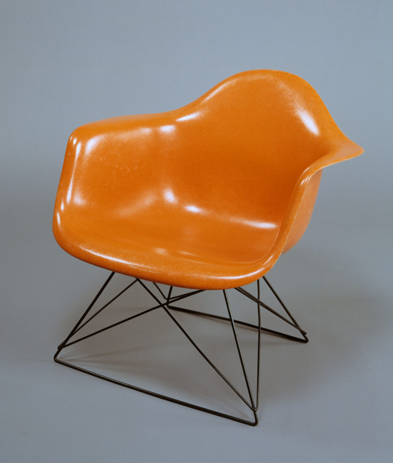 Large molded shell armchair in orange fiberglass with a crisscrossing base of black wire.