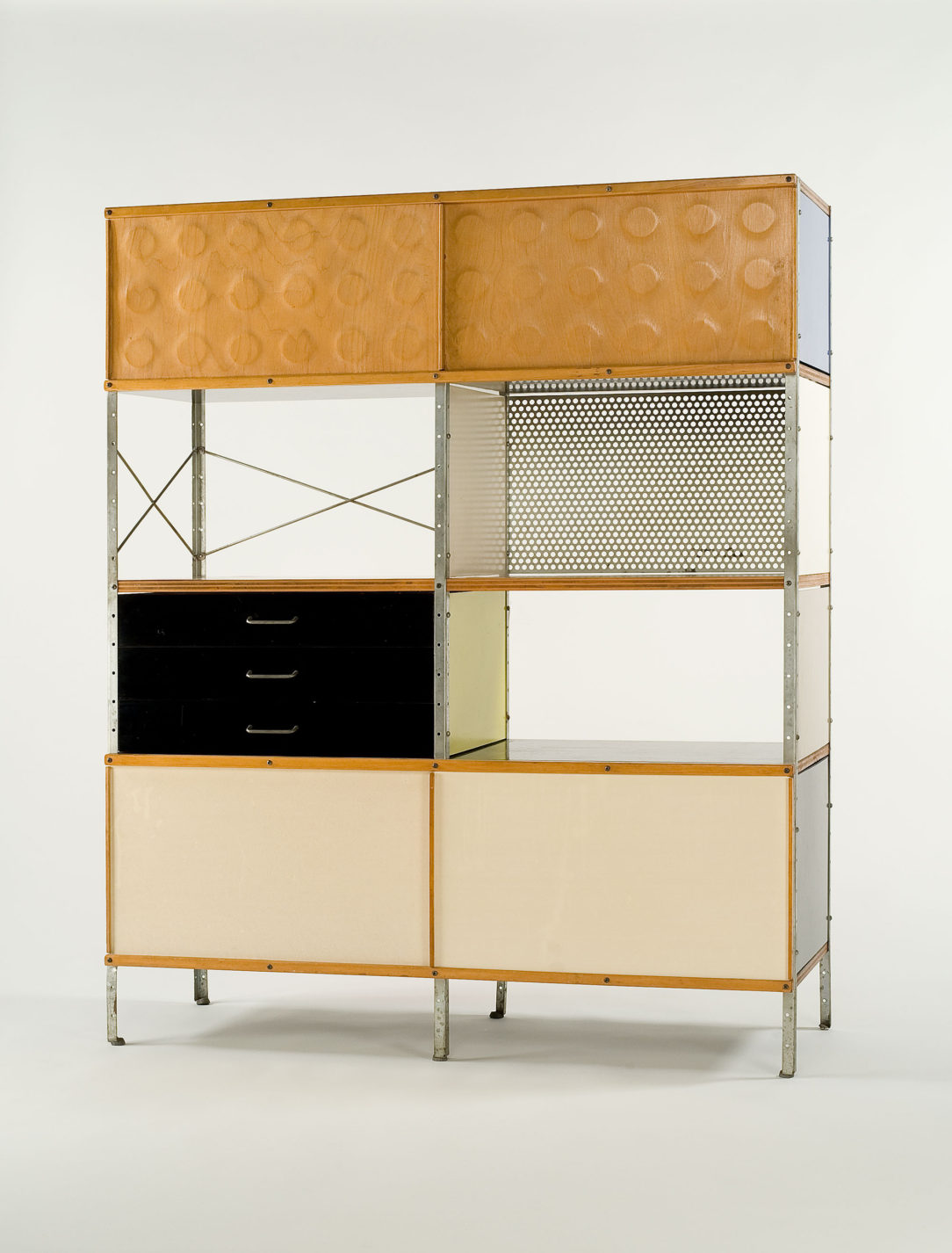 Tall storage unit with a steel frame and modular drawer, cabinet, and shelf components in different materials and colors.