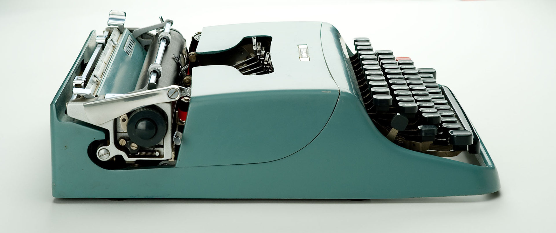 Blue metal typewriter. Its open keyboard has dark grey keys and a red carriage return key. The bar for holding the paper in place and the ruler for measuring margins are in shiny metal.