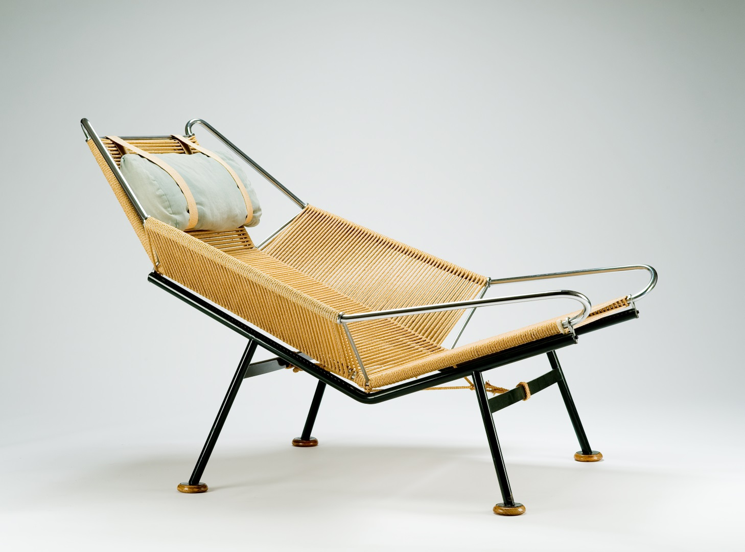 Semi-reclined lounge chair with seat, back, and arms made of rope wrapped around a chromed and black metal frame with four legs.