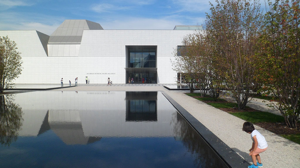 Large white building with an angled dome and a large glass entryway and a reflecting pool in the foreground.