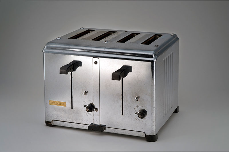 Four-slice toaster. Simple box of shiny metal with black levers and controls on the front.
