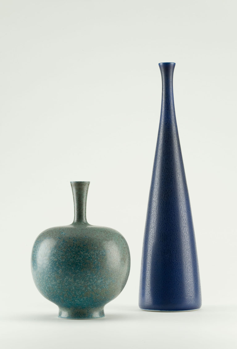 Two glazed stoneware vases. A short, round one in teal blue with a slender mouth that flares at the top, and a tall one in medium blue with an elongated cone-shaped body and a small flared mouth.