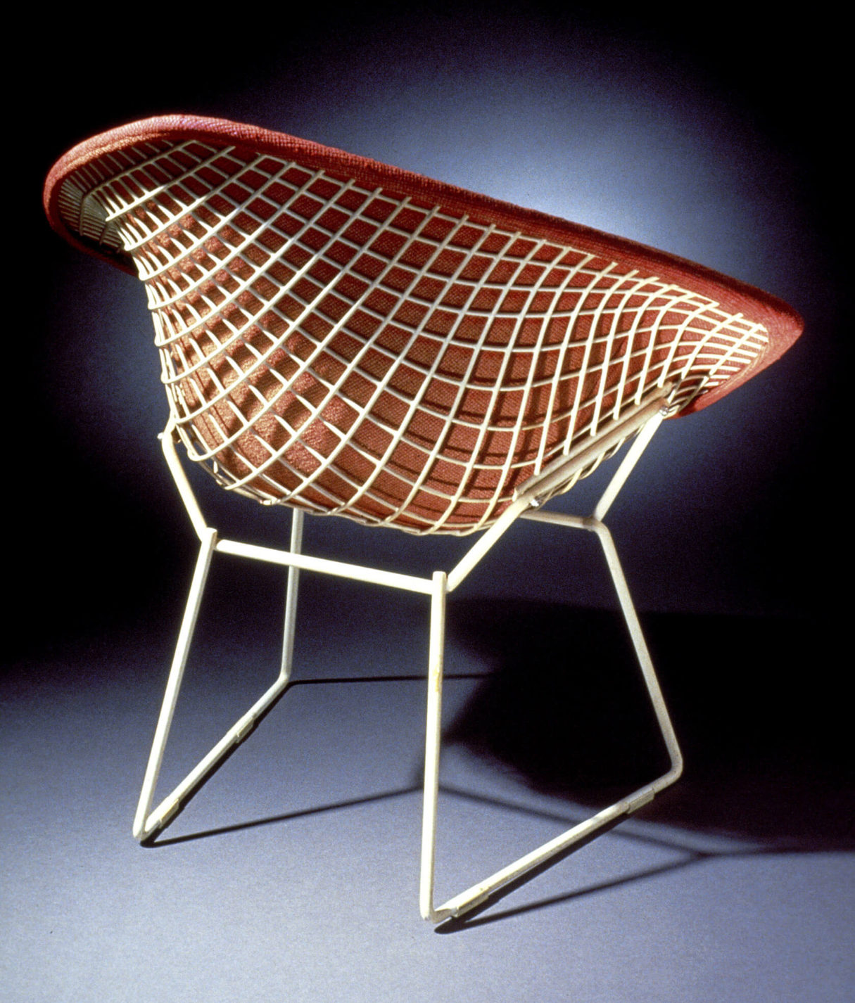 White wire-framed armchair viewed from the back. Seat, back, and arms are formed from an open wire mesh and covered on the front with red upholstery.