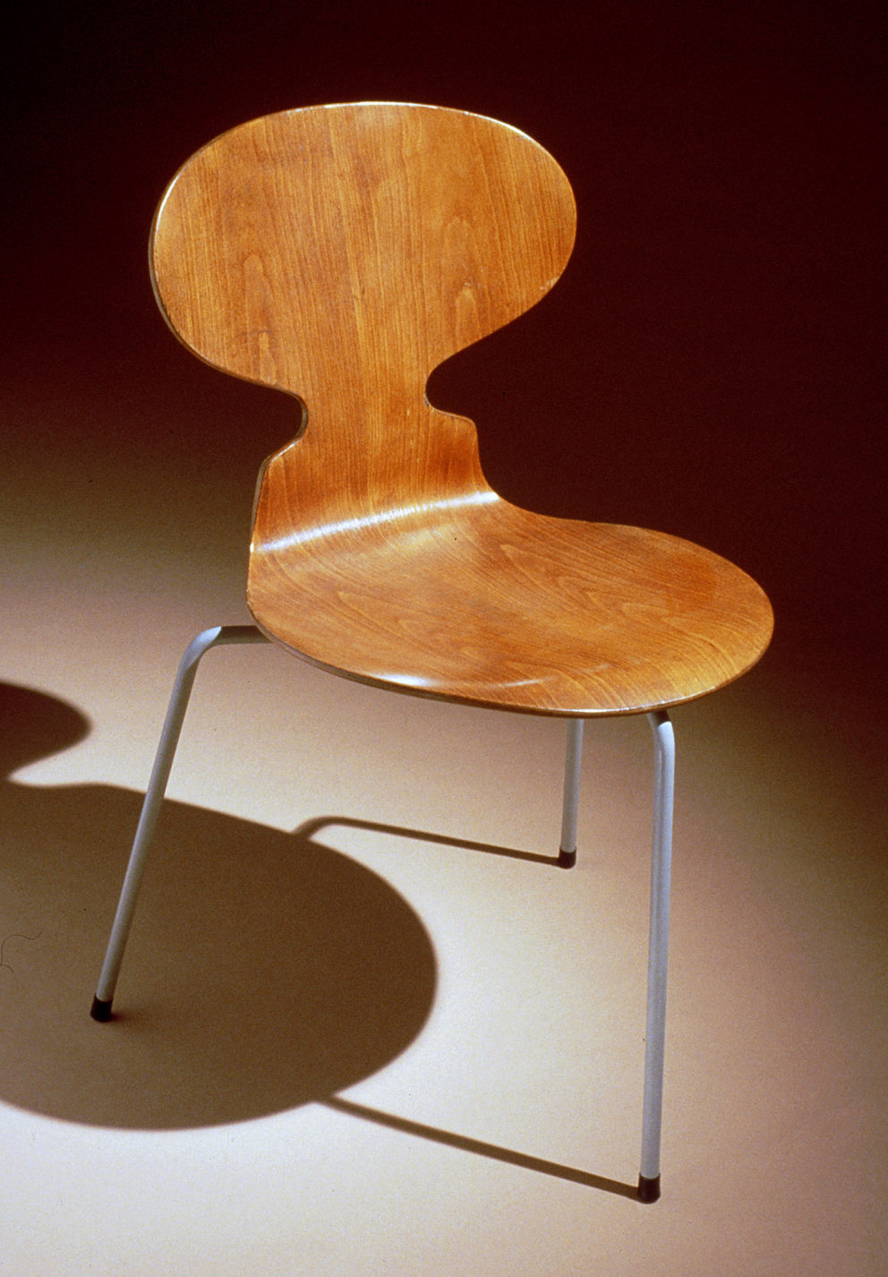 Chair with a single piece of plywood bent to form the oval back and round seat supported by three steel tubular legs.