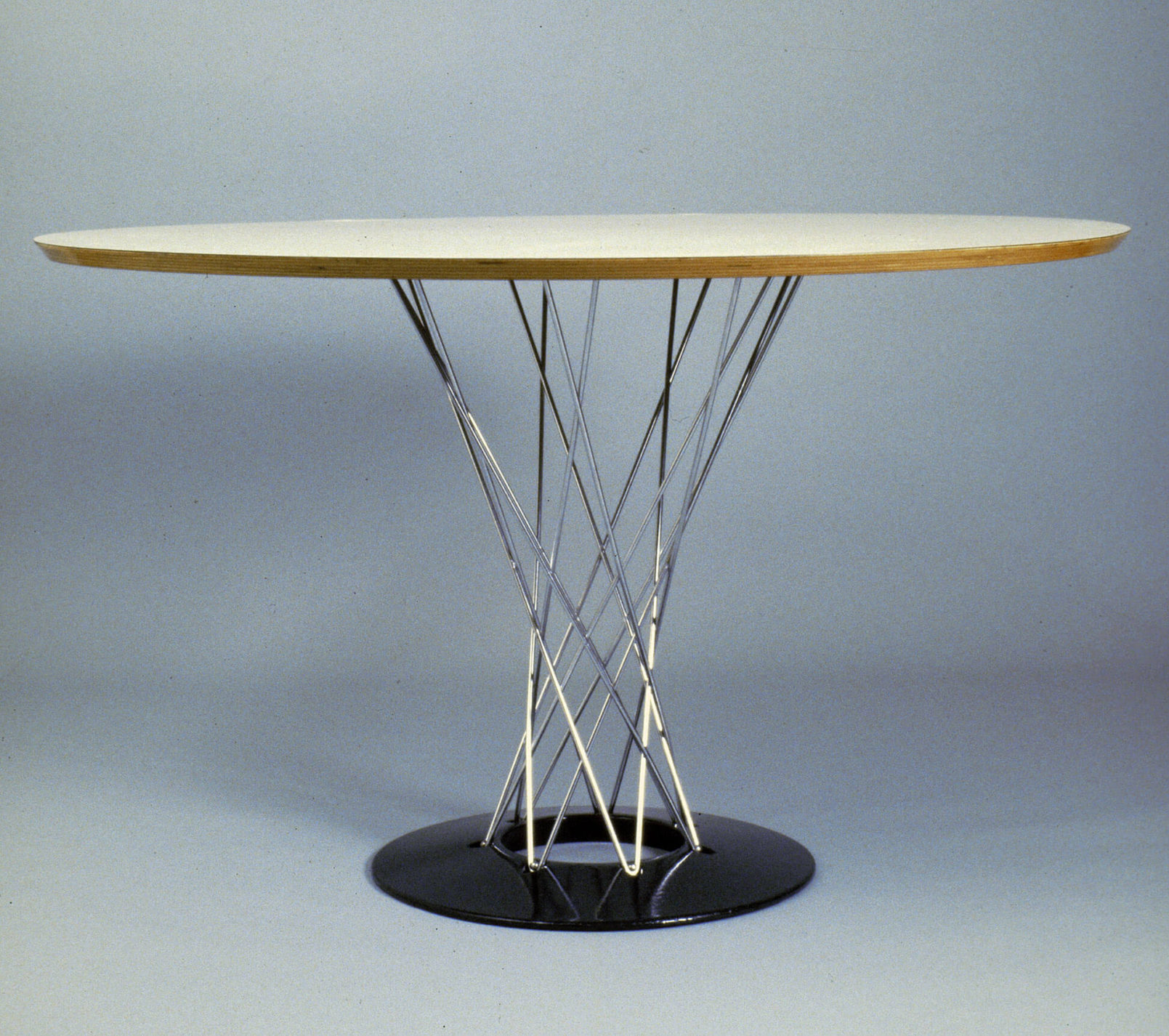 Circular table with white surfaced and wood-edged top on a crisscrossing steel wire and black disc base.