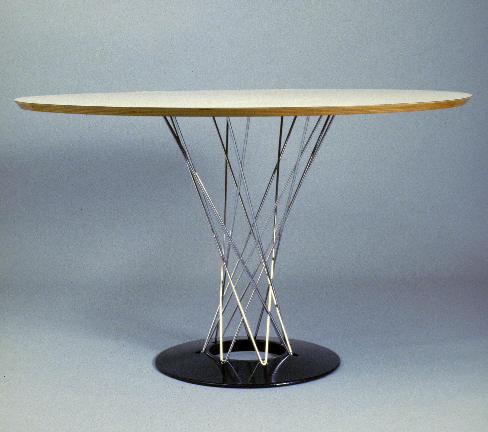 Table circulaire à surface blanche au rebord en bois reposant sur un entrelacement de tiges d'acier et un disque noir au sol.