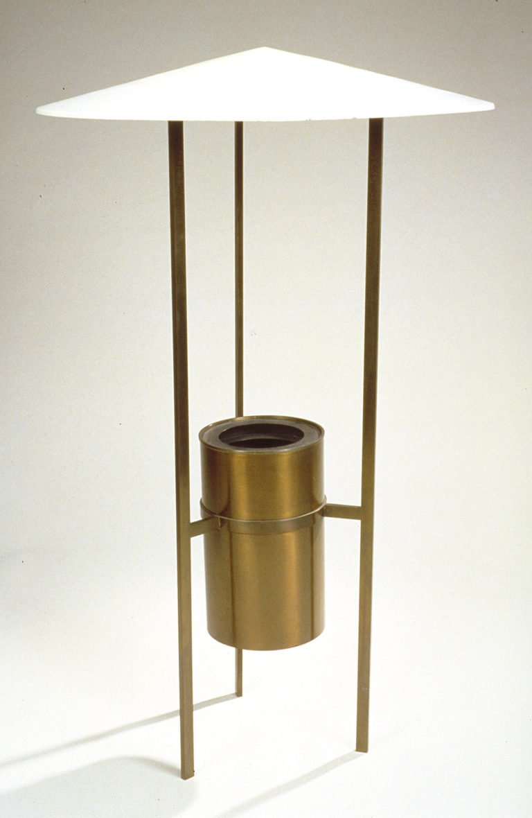 Floor lamp with three slender bronze legs and with a cylinder suspended between them and a shallow cone shade at the top in opaque white.