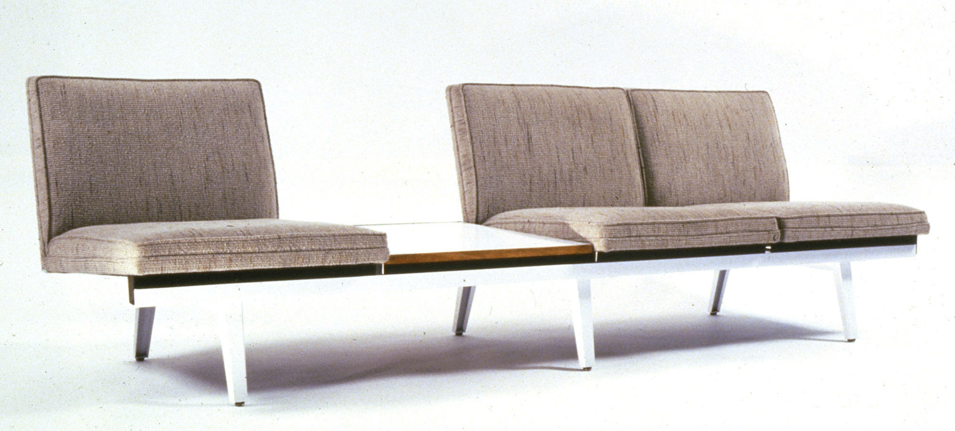 Armless sofa with three seats with tan seat and back cushions on a low steel bench. Between two of the seats is a white Formica table surface.