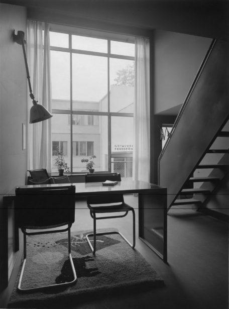 Photo d'exposition en noir et blanc où l'on peut voir des chaises d'appoint de Markelius et d'autres meubles modernes bordés d'un escalier.