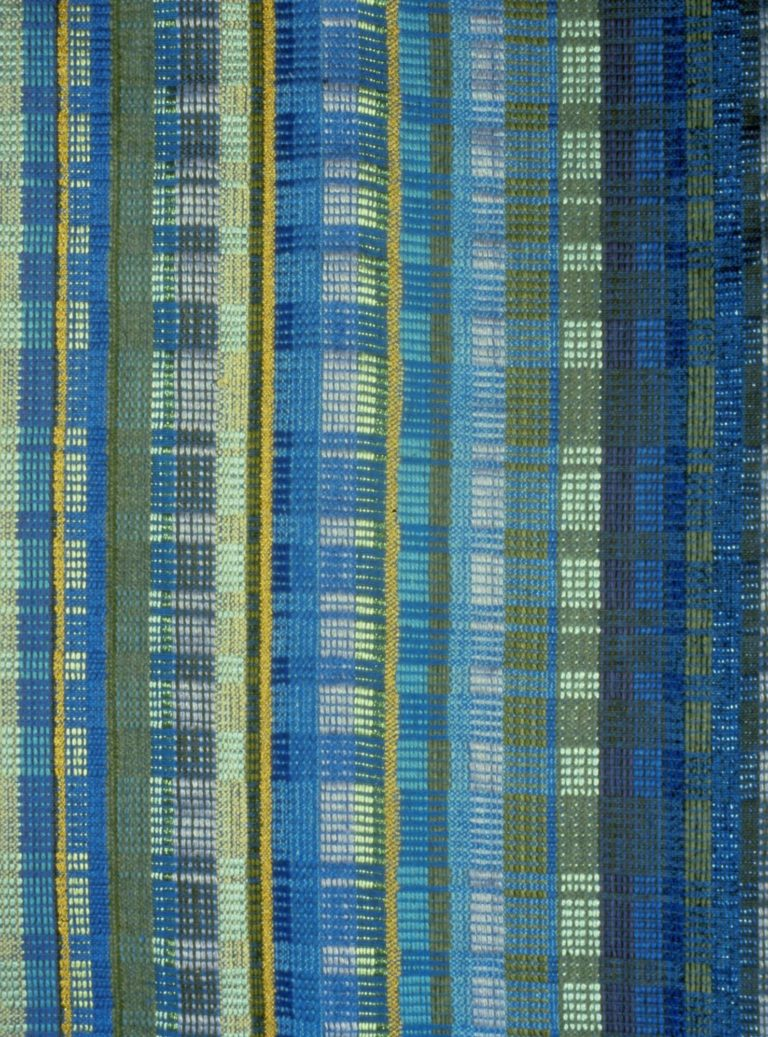 Textile with block pattern in various shades of blue, green, grey, and yellow.