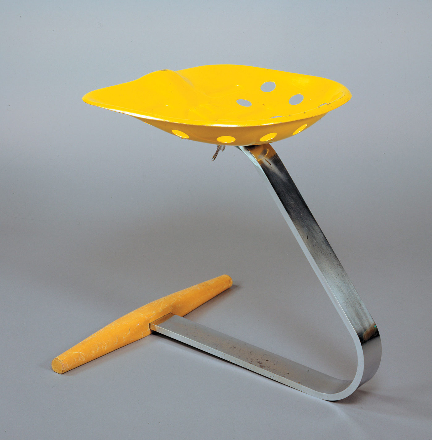 Stool with a wood and strap-steel base supporting an old-fashioned metal tractor seat in bright yellow.