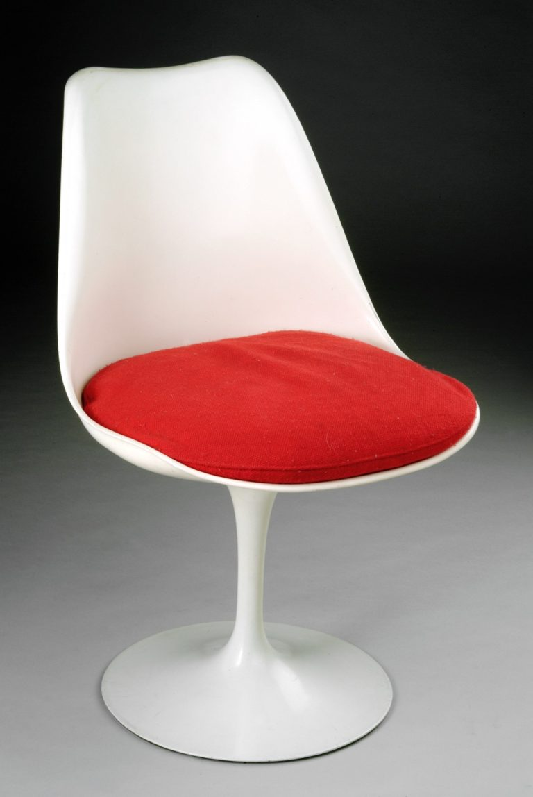 White plastic shell chair with a red cushion supported by a slender stem and a flared circular base.