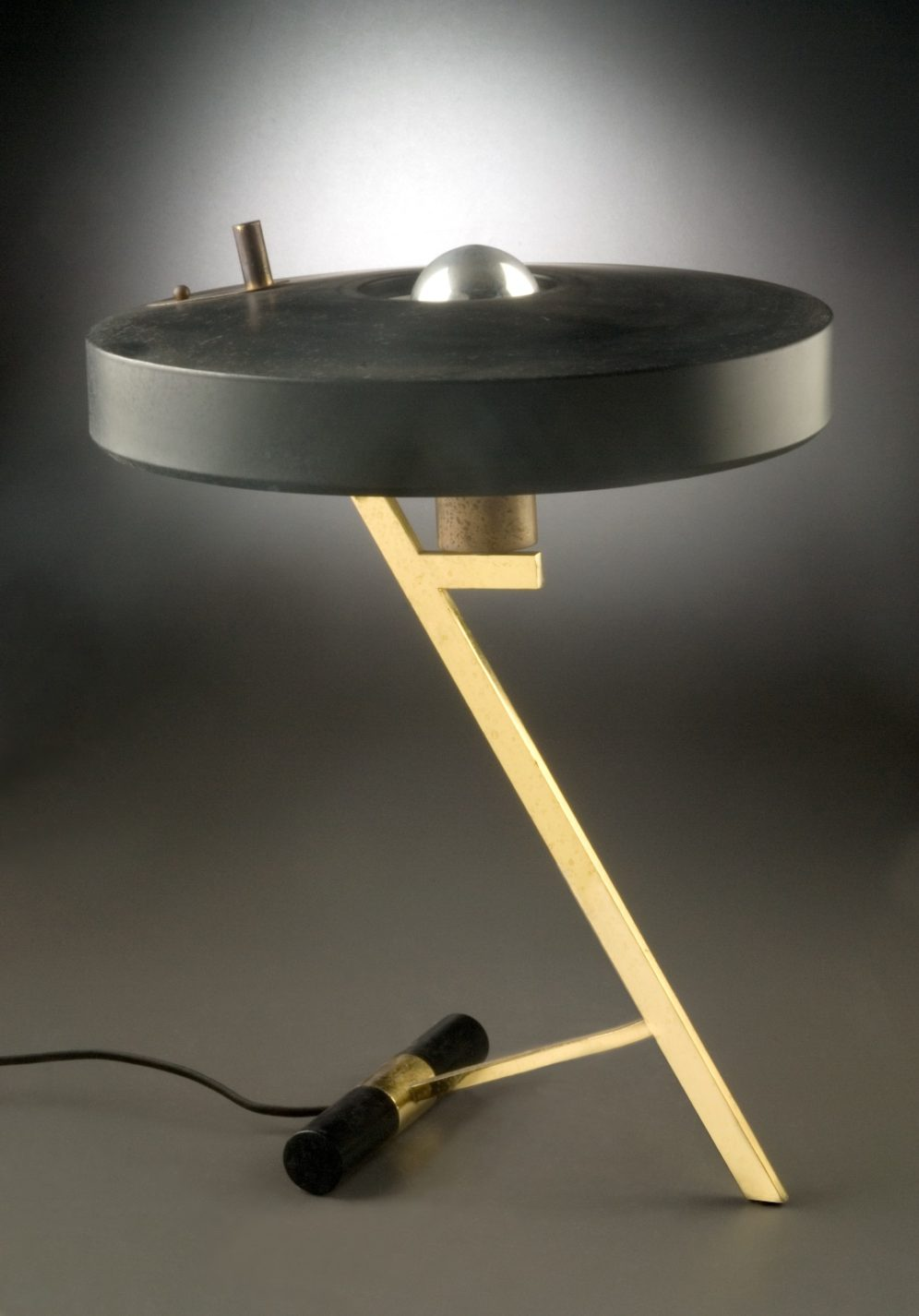 Table lamp with angled brass shaft and shallow cylindrical black aluminum shade.